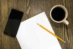 Téléphone de papier et une tasse sur la table Images stock