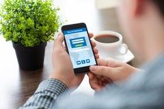 Téléphone de participation d'homme avec le réseau social sur l'écran en café Images stock