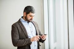 Téléphone de participation d'homme - jeune homme d'affaires utilisant le smartphone dans le bureau Photographie stock
