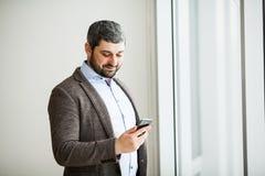 Téléphone de participation d'homme - jeune homme d'affaires utilisant le smartphone dans le bureau Photos libres de droits