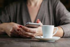 Téléphone de participation de femme de main et tasse de café photo stock