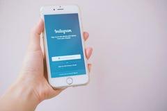 Téléphone de participation de main montrant l'instagram Image libre de droits