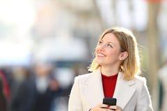Téléphone de participation de femme pensant et regardant le côté Photo libre de droits