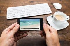 Téléphone de Person Watching Video On Mobile Photos stock