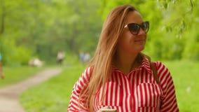 Téléphone de prise de femme enceinte dans une main, rapidement type message et sourires à la caméra, marchant le parc Tir moyen banque de vidéos