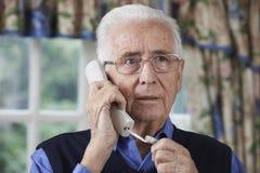 Téléphone de réponse inquiété d'homme supérieur à la maison Photographie stock