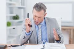 Téléphone de réponse irrité d'homme d'affaires images stock