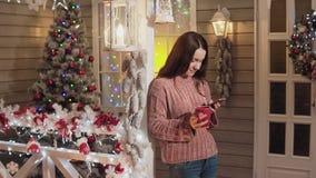 Téléphone de sourire d'utilisation de thé de boissons de femme au porche avec l'arbre de Noël au fond banque de vidéos