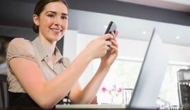 Téléphone de sourire de participation de femme d'affaires regardant l'appareil-photo Photographie stock