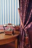 Téléphone de vintage sur la table près du mur avec le papier peint rayé Photographie stock