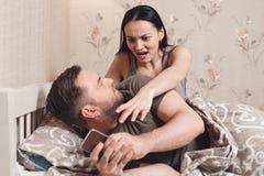 Téléphone du ` s d'épouse de montre de mari dans le lit Photographie stock libre de droits