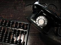 Téléphone et abaque antiques de cadran sur la table en bois Images stock