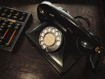 Téléphone et abaque antiques de cadran sur la table en bois Photographie stock libre de droits