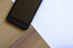 Téléphone et bloc-notes Photo stock