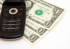 Téléphone et dollars Photographie stock