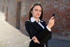 Téléphone et glaces de fixation de femme d'affaires Image stock