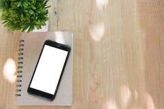 Téléphone et livre futés sur le fond en bois de table avec l'espace de copie Photos stock