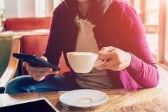 Téléphone et tasse de participation de femme de main dans le café Photo stock