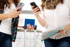 Téléphone femelle de participation de main de plan rapproché, passeport, une carte et bagage touristes Image stock