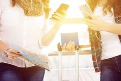 Téléphone femelle de participation de main de plan rapproché, passeport, une carte et bagage touristes Photographie stock libre de droits