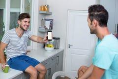 Téléphone gai d'apparence d'homme à l'ami Image stock