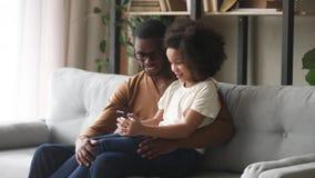Téléphone heureux de participation de fille d'enfant se reposer sur le recouvrement africain de papa clips vidéos