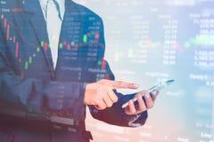 Téléphone intelligent émouvant de doigt d'homme d'affaires avec des finances et des opérations bancaires photos stock