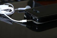 Téléphone intelligent avec des écouteurs Photographie stock