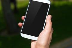 Téléphone intelligent avec l'écran noir sur le fond naturel Photos stock