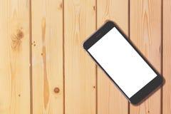 Téléphone intelligent avec l'écran vide sur le fond en bois de table avec la Co photographie stock