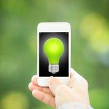 Téléphone intelligent avec l'ampoule photographie stock
