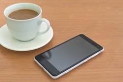 Téléphone intelligent avec la tasse noire d'écran et de café sur le bureau en bois Photos libres de droits
