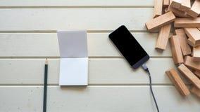 Téléphone intelligent avec le carnet et le bloc en bois Photographie stock