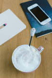 Téléphone intelligent avec le carnet et la tasse de café fort sur le CCB en bois Image stock