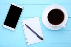 Téléphone intelligent avec le carnet et la tasse de café sur le fond en bois bleu photo libre de droits