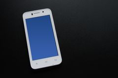 Téléphone intelligent blanc avec l'écran bleu sur le Tableau noir Images libres de droits