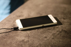 Téléphone intelligent blanc de remplissage sur le bureau de graphite Photographie stock libre de droits