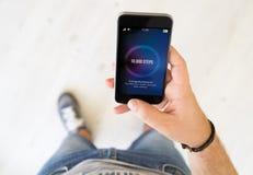 téléphone intelligent d'étapes masculines de la main 10000 image libre de droits