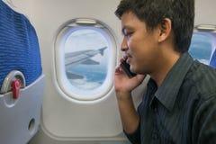 Téléphone intelligent d'utilisation d'homme dans l'avion Photographie stock libre de droits