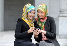 Fille de deux écharpes à l'aide du téléphone intelligent images libres de droits