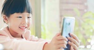 Téléphone intelligent d'utilisation de fille heureusement photo libre de droits