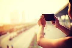 Téléphone intelligent d'utilisation de mains de femme extérieur Photo stock