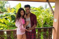 Téléphone intelligent de cellules d'utilisation de couples sur la terrasse, l'homme et la femme d'été embrassant le sourire heure Photos stock