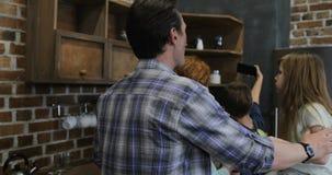 Téléphone intelligent de cellules d'utilisation de fils prenant le portrait de selfie de la famille heureuse dans la cuisine ense banque de vidéos