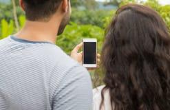 Téléphone intelligent de cellules de prise d'homme et de femme avec l'écran vide, vue arrière de dos au-dessus de Forest Landscap Photo libre de droits