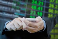 Téléphone intelligent de contact d'homme d'affaires à disposition avec du Ba de tache floue de taux de change Photographie stock libre de droits
