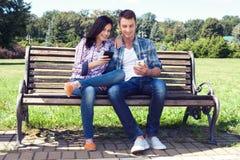 Téléphone intelligent de observation stupéfait jeunes par couples extérieur Photo libre de droits