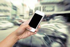 Téléphone intelligent de prise de main de femme, comprimé, téléphone portable sur le mouvement de tache floue Photos stock