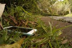 Téléphone intelligent perdu le long d'une route photo libre de droits