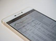 Téléphone intelligent sur des graphiques de table des marchés financiers pour la croissance du bitcoin et d'autres crypto-devises Photos libres de droits